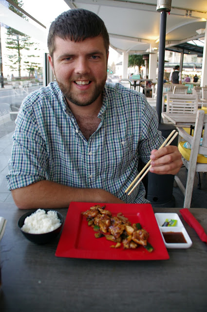 dan tucking into dinner with chop sticks