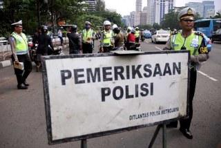 Petugas memeriksa kelengkapan surat-surat kendaraan sejumlah pengendara yang melintas dikawsan Kampung Melayu Jakarta Timur, pengendara yang surat-surat kendaraannya tidak lengkap langsung di tilang dengan menggunakan sistem tilang elektronik atau E-Tilang