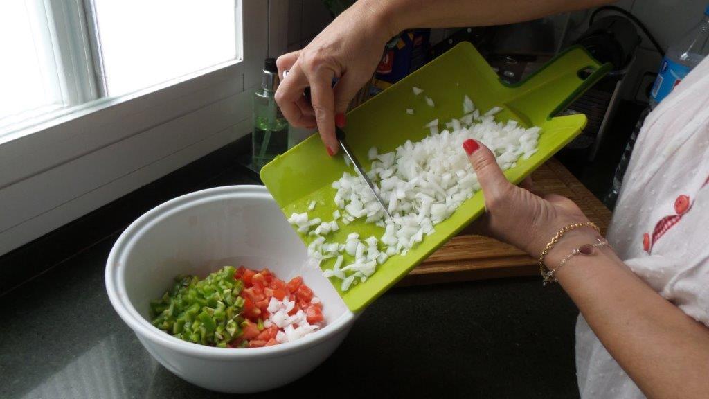 Mezcla de la cebolla con el pimiento y el tomate