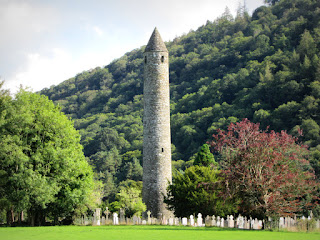 A tall stone round tower with a cemetery and trees at its feet and a hillside in the background.