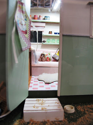 Interior of a one-twelfth scale miniature vintage caravan, with a kiwi stuffed toy on the seat.