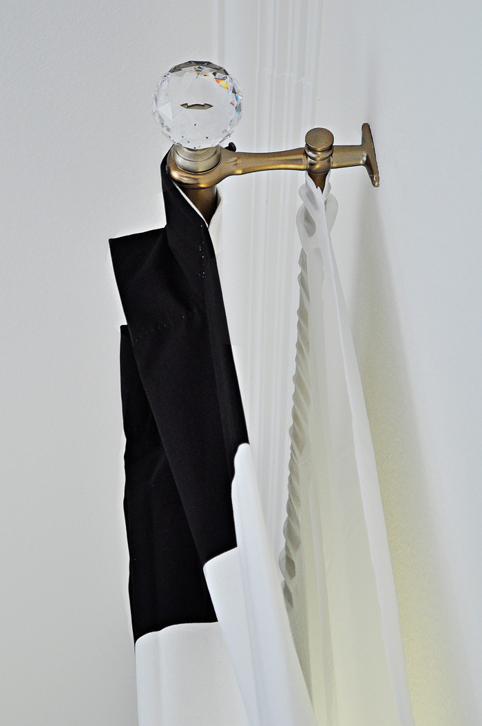 Black and white striped draperies hung on a gold/brass curtain rod. | via monicawantsit.com