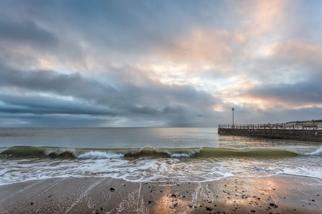 Beautiful clouds at sunrise with waves lapping onto Swanage beach