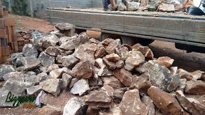 Pedra moledo com tamanhos variados e cores mescladas, para construção de torre de pedra.