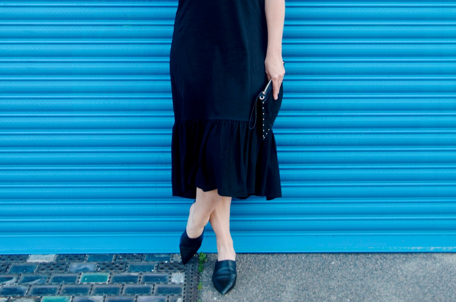 Black ruffle hemmed midi dress, black suede clutch and black pointed toe mules
