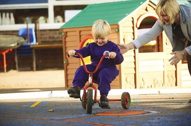 My Little Boy riding a bike at his nursery, in his purple jumpsuit