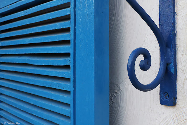 A Minimalist Photograph of a Blue Metal Curl Shown in contrast with Simple Lines of a Window.