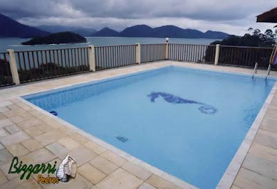 Construção da piscina de alvenaria com o passeio da piscina em pedra São Tomé e o revestimento da piscina com azulejo azul. Piscina construída de frente para o mar em cima de 2 pilares, sendo o mais alto com 20 m acima do nível da terra.