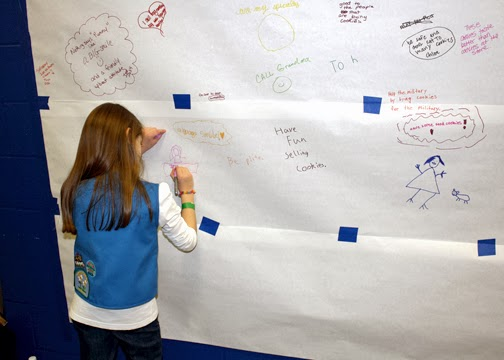 Tessa drew a picture of her at a cookie booth on the community share-a-cookie-selling-tip wall at Cookie Rally 2014.