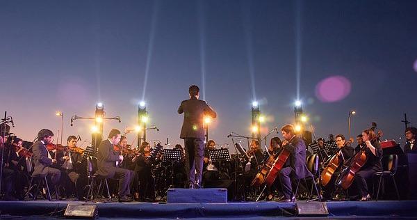 orquesta sobre escenario al aire libre, atardecer, iluminado por focos