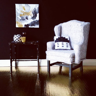 One-twelfth scale modern miniature scene in gold, black, and white comprising a gold-coloured floor and black wall. A grey and black wing chair displays a black and white stitched cushion, and next to it is a black bamboo side table holding three vases in gold, black and white. On the wall above it is a piece of modern art in grey, black, white and gold.