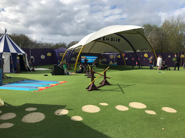 A large display area with artificial grass, games, a tent, stepping stones and stage area
