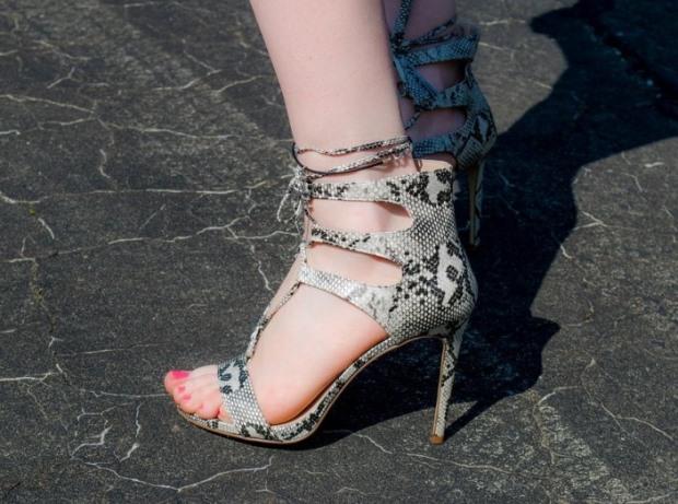 feet wearing snakeskin heels