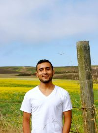 Image of Javier Zamora standing outdoors with a barbed wire fence and field behind him, with hills in the distance. He is wearing a white, v-neck t-shirt. He has short, dark hair and a light beard.