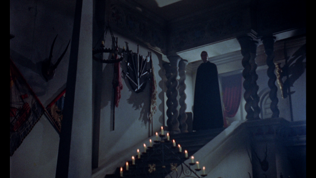 dracula at the top of the staircase waiting to make his grand entrance