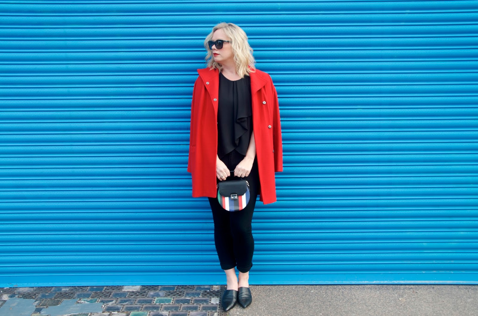 blue wall, red coat, striped bag and all black outfit