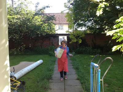 Picture of me in an apron, carrying a box down the front path on moving day when we moved to the country