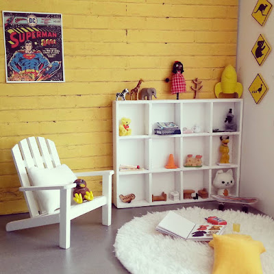 One-twelfth scale modern miniature playroom with concrete floor and yellow brick wall. A white-painted cube bookcase displays toys next to a white chair.