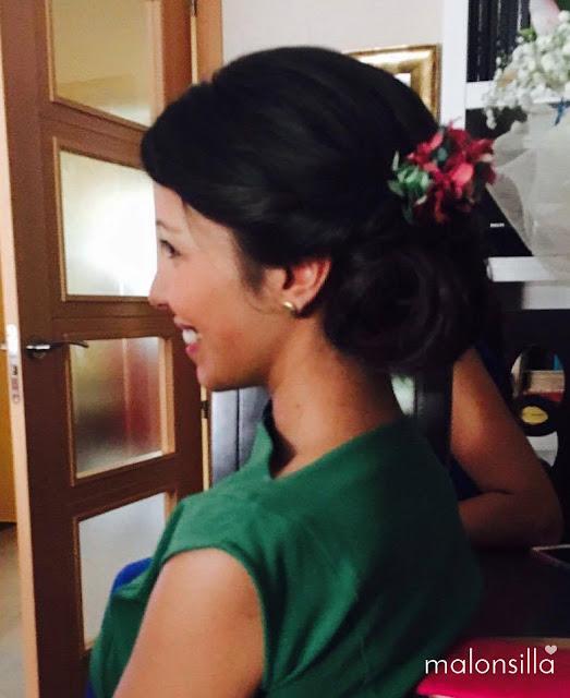 Invitada boda con recogido bajo de perfil con tocado tipo peineta de flores en colores verde esmeralda y fucsia buganvilla, vestido verde esmeralda