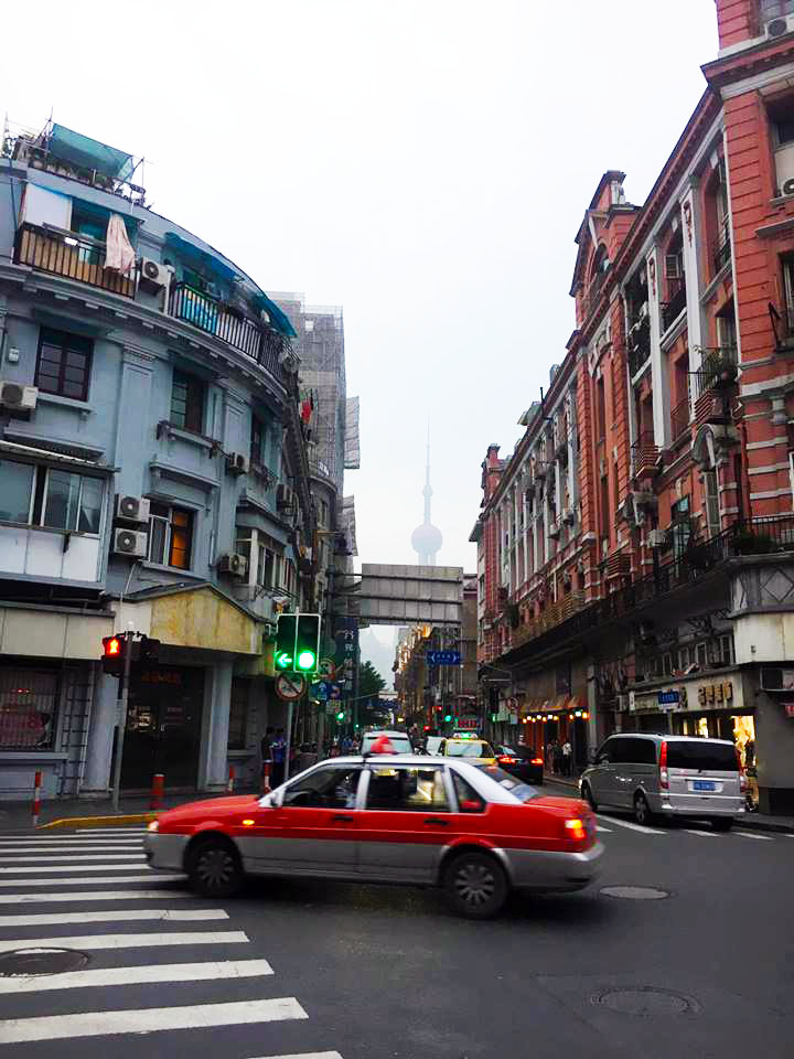 taxi in busy street in Shanghai with oriental pearl tv tower in distance