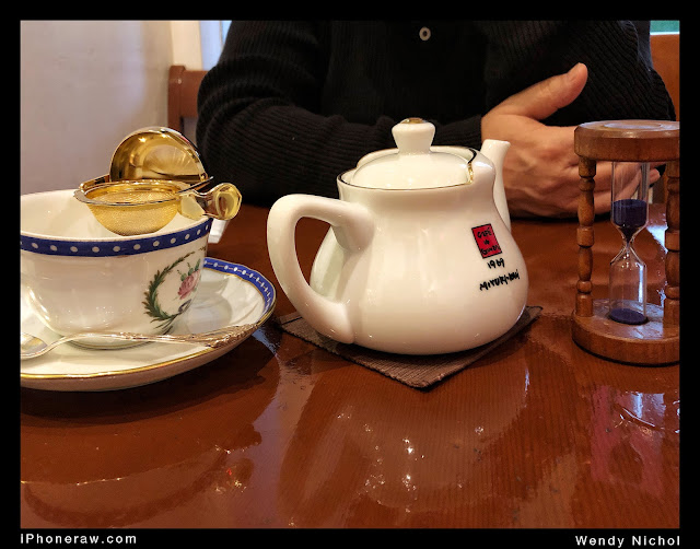 Tea with a gold strainer and a timer.