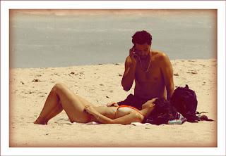 Imagen de un hombre y una mujer acostados en la arena de la playa