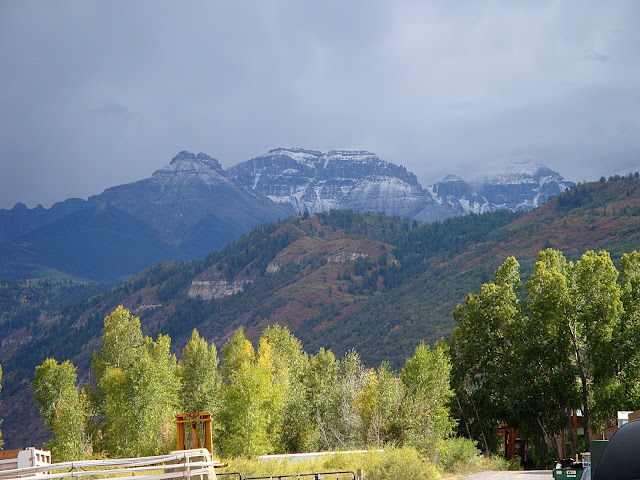 Mountains with a dusting of snow towering over aspens beginning to turn yellow.