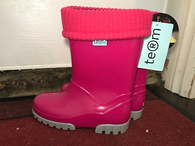 A pair of pink wellies with a roll top liner and labels still on next to a front door