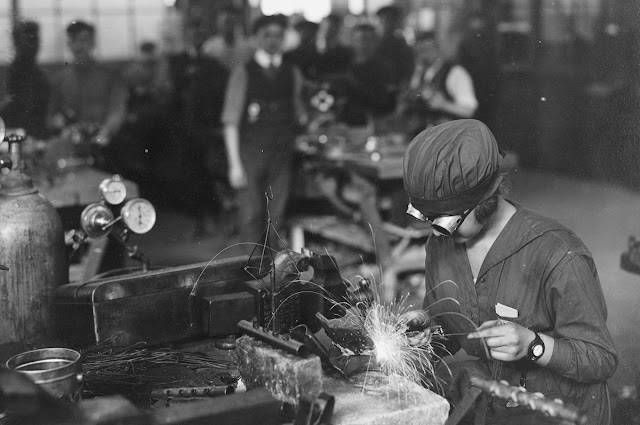 Original caption: Running the welding machine. War time women workers in naval aircraft factory in Philadelphia, Pennsylvania, circa 1918.