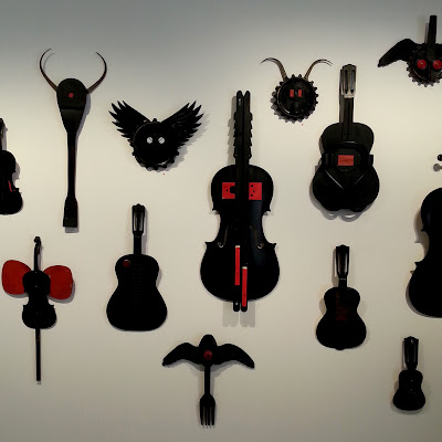 View of an art gallery exhibition with a wall full of Alex Asch assemblage art pieces in black and red, based on various musical instruments.