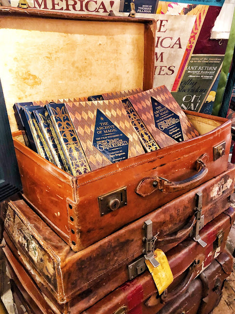 A pile of brown leather suitcases. The top one is open and contains the House of Mina Lima Crimes of Grindelvald book. The book is brown and gold with a big blue diamond on the front and the text is gold