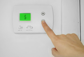 A finger lowering a thermostat that is displaying a money symbol in Middletown, NY