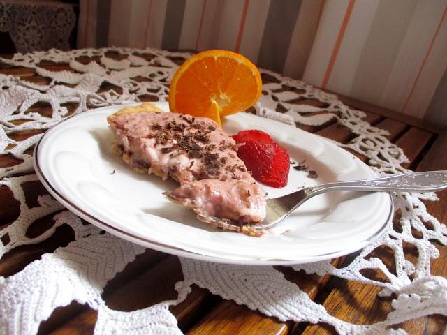 rebarbarahabos sütemény szelet  tányéron   eperrel ,naranccsal villával