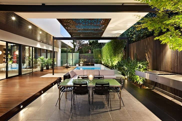 Dining table in Beautiful modern backyard by Cos Design