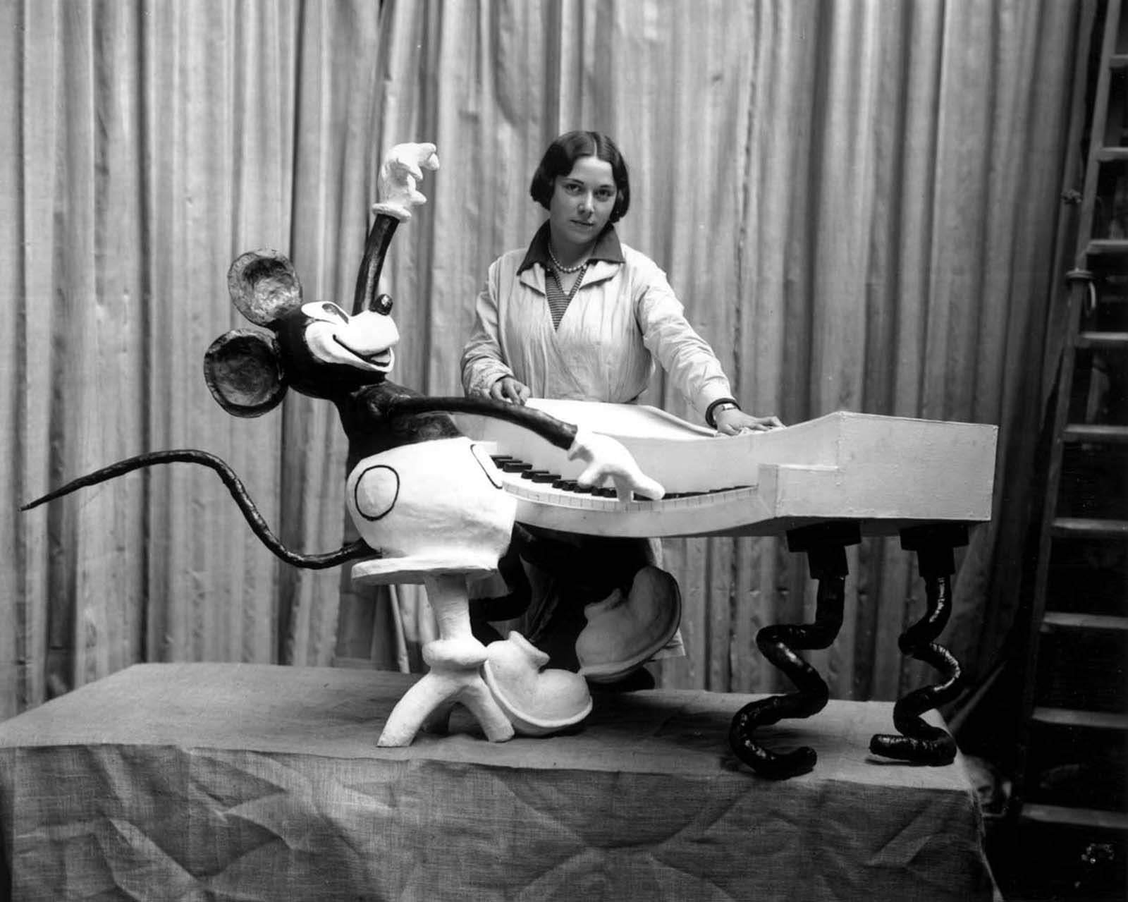 An employee at Madame Tussaud's waxworks museum on Marylebone Road, London, putting the finishing touches to a waxwork of Mickey Mouse at the keyboard. 1930.