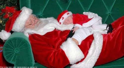 witziger Weihnachtsmann schläft mit Baby auf Bauch - Weihnachtsfotos lustig