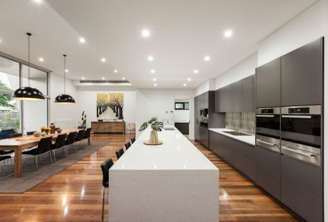 The spacious, luxurious kitchen is connected with a long dining table