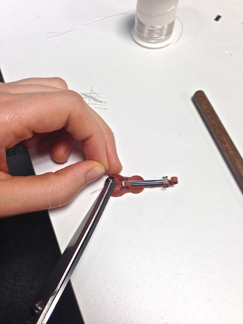 attaching strings onto a quilled violin