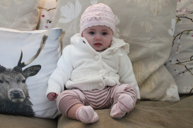 baby wearing pink & purple stripe trousers with thick white cardigan and pink knitted hat