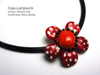 rot-orange Glasbluete mit Polka Dots