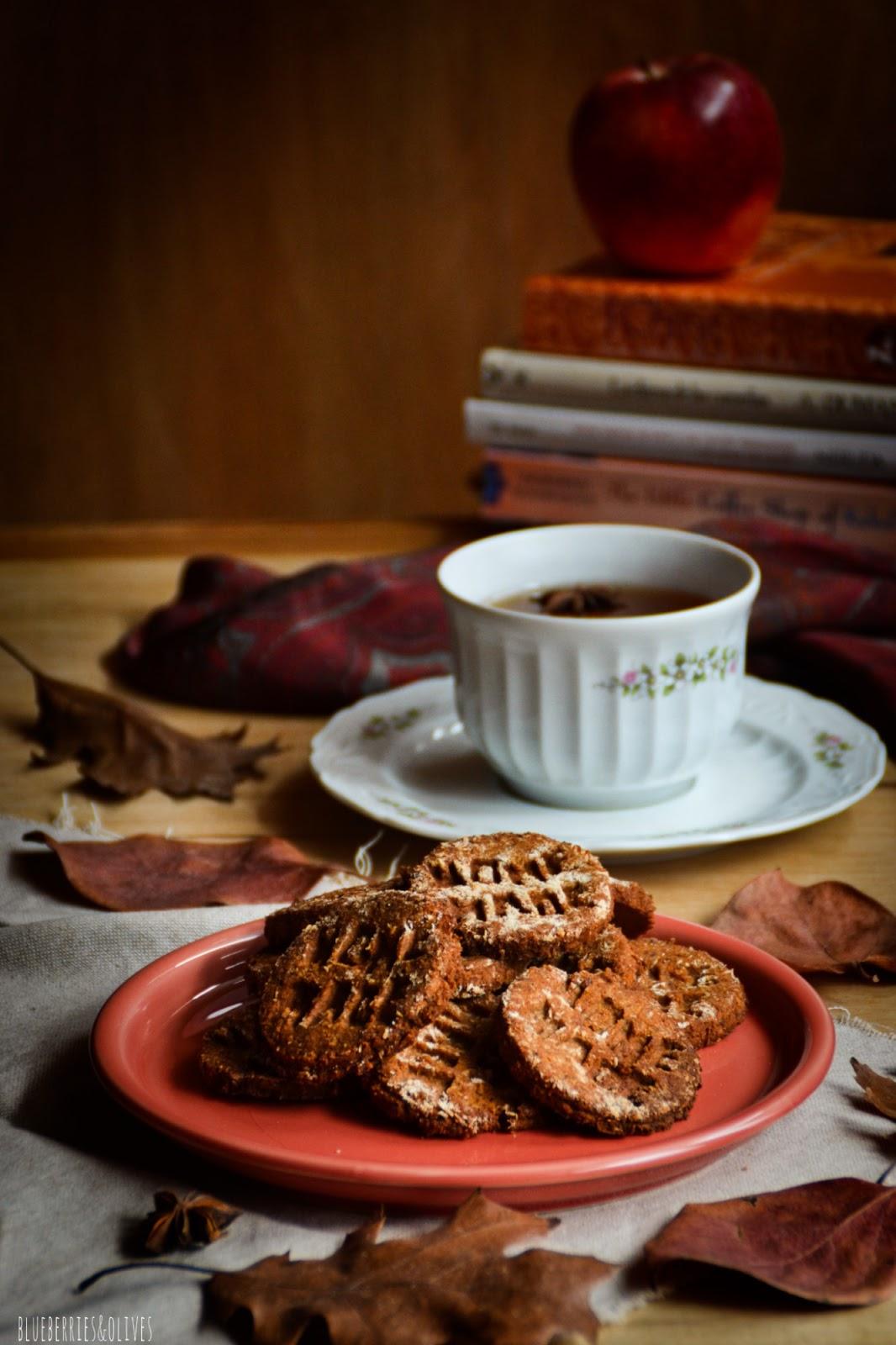 Galletas caseras sobre plato cerámica rojo, fondo madera oscuro, manzanas rojas, hojas secas otoño, paño de lino beige