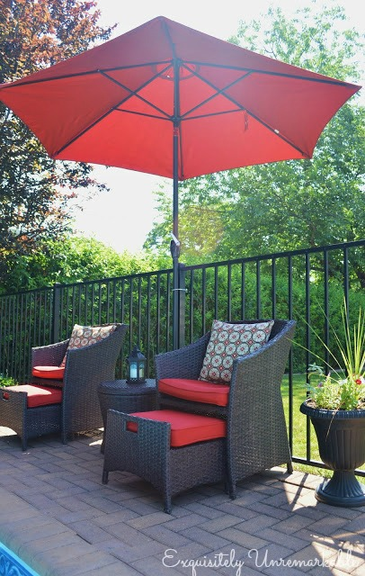 Wicker chairs with red cushions and pillows under a red umbrella