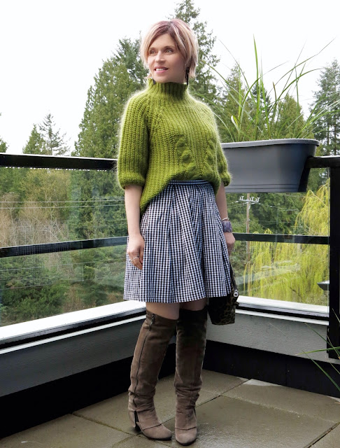 styling a gingham skirt with a funnel-neck mohair sweater, over-the-knee boots, and leopard clutch