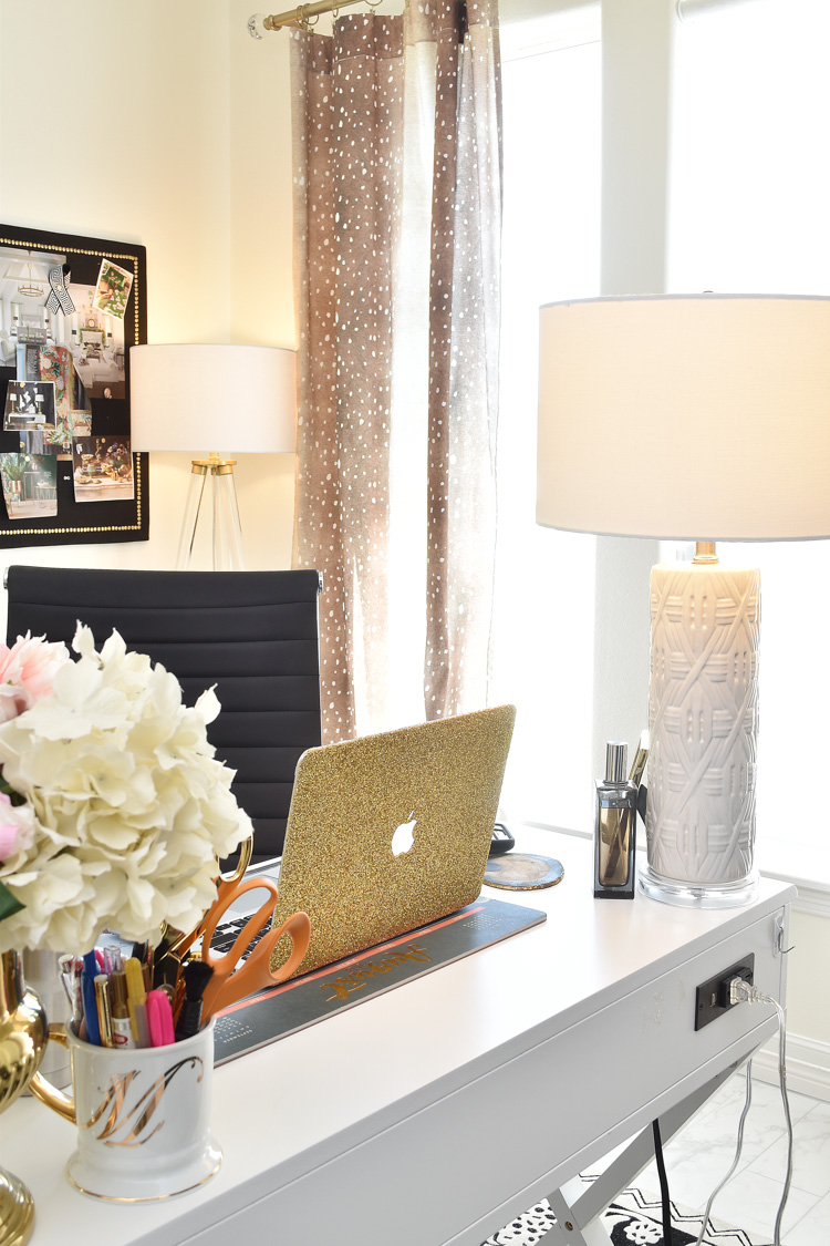 A sleek and feminine white and gold home office with fawn and antelope curtains and black, white and gold decor.