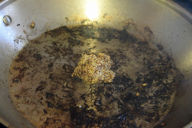 The skillet on the stove with the mustard being added to it.