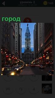 В свете огней показана одна из улиц большого города с высокими зданиями