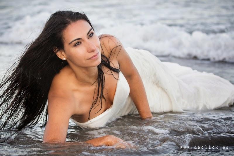novia vestida mojándose el traje tirada en la arena