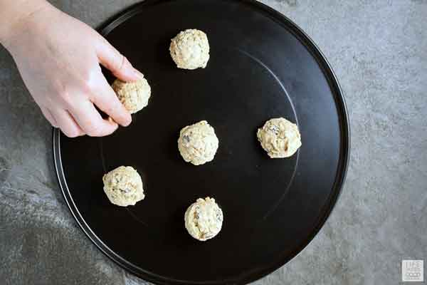 Frozen Quaker Oatmeal Cookie dough balls being placed on a baking tray
