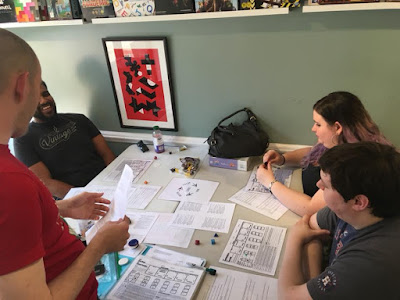 A shot looking down at a table with papers strewn about it. An adult male (Duffy Austin) stands as he talks to an adult male playtester who is laughing. They are to the left of the photo. To the right are an adult male and adult female who are sitting at the table.