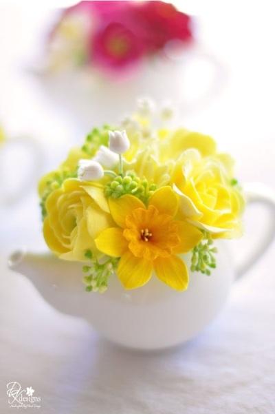 Cantiknya teko putih jadi vas bunga kuning yang cerah.